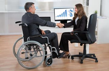 man in a wheelchair and woman shake hands with graphs on a computer in the background